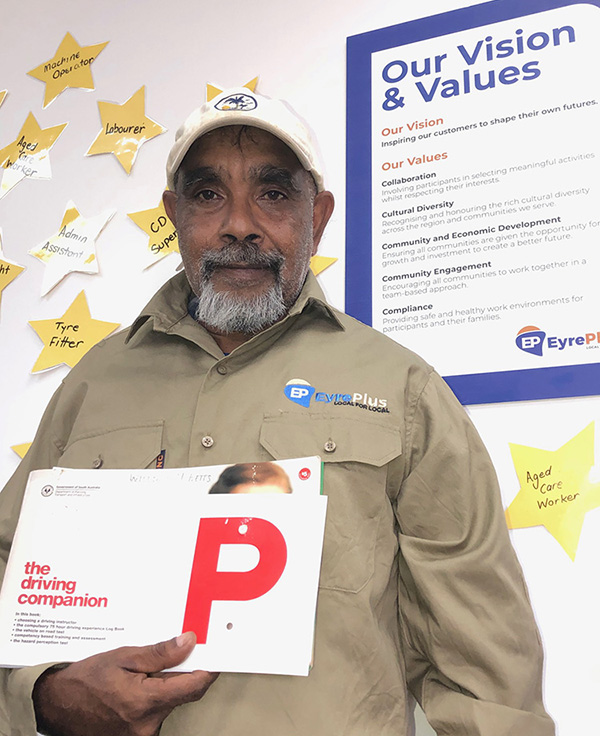 EyrePlus Participant Billy holding up his P plates inside the EyrePlus office