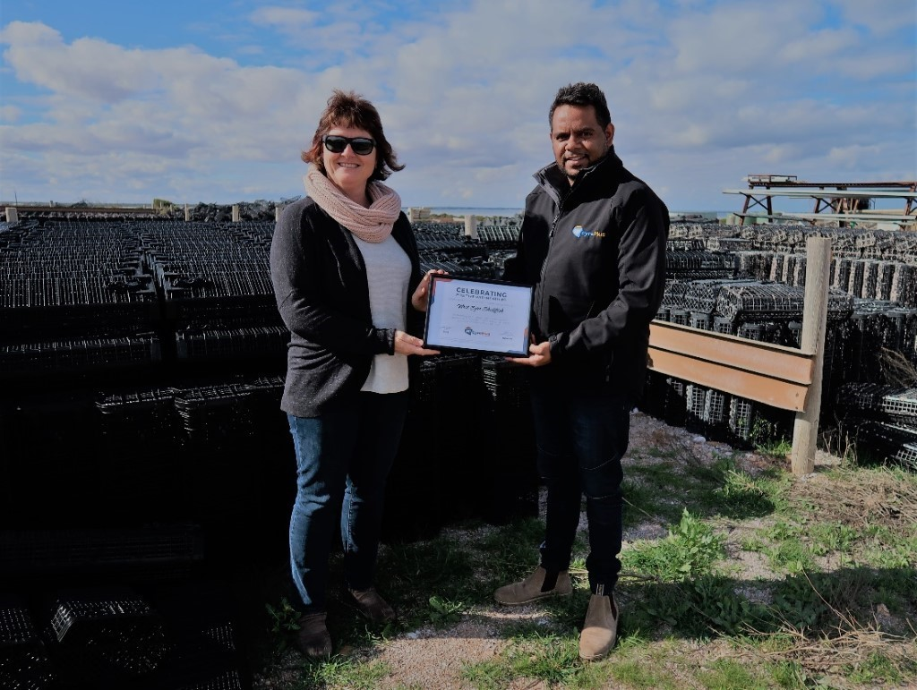 Wendy from West Eyre Shellfish receiving a certificate of gratitude from EyrePlus Compliance Officer, Randy, in front of West Eyre Shellfish's Hexcle Systems baskets