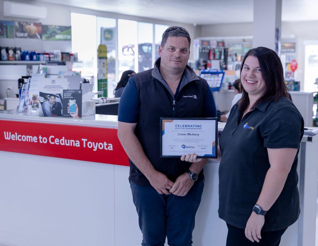 Matthew from Ceduna Machinery standing alongside EyrePlus post placement support officer Megan receiving a certificate inside Ceduna Toyota